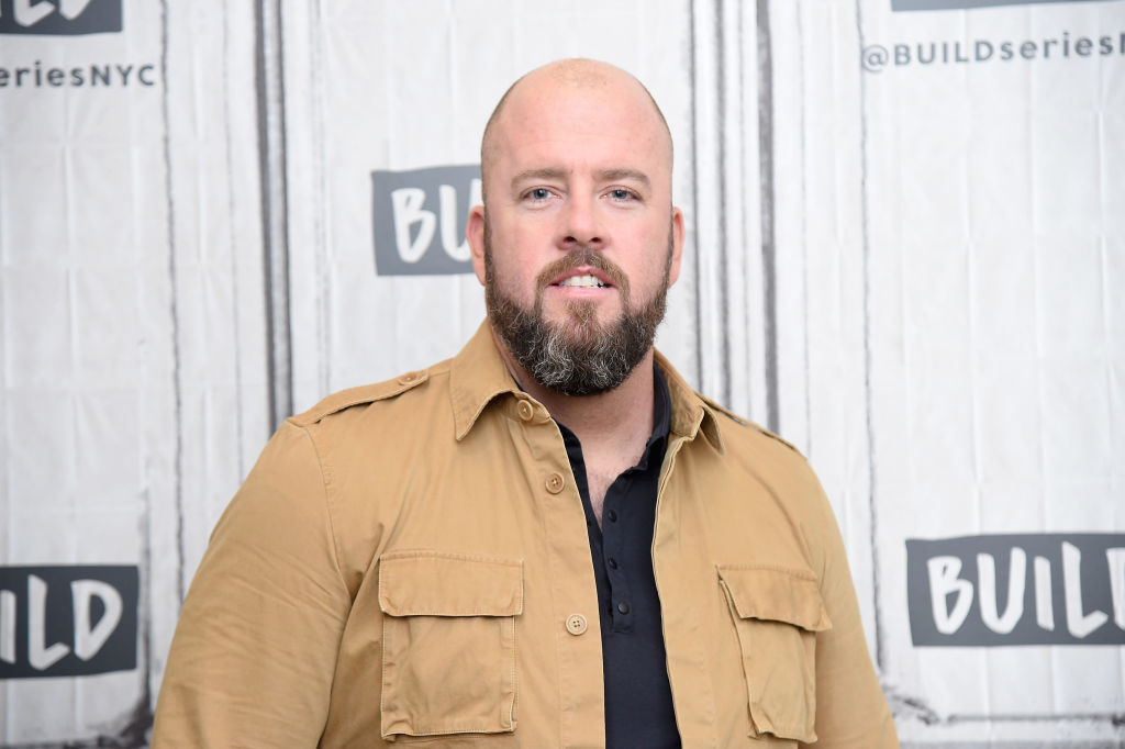 Chris Sullivan walks the red carpet in a black shirt and tan jacket.