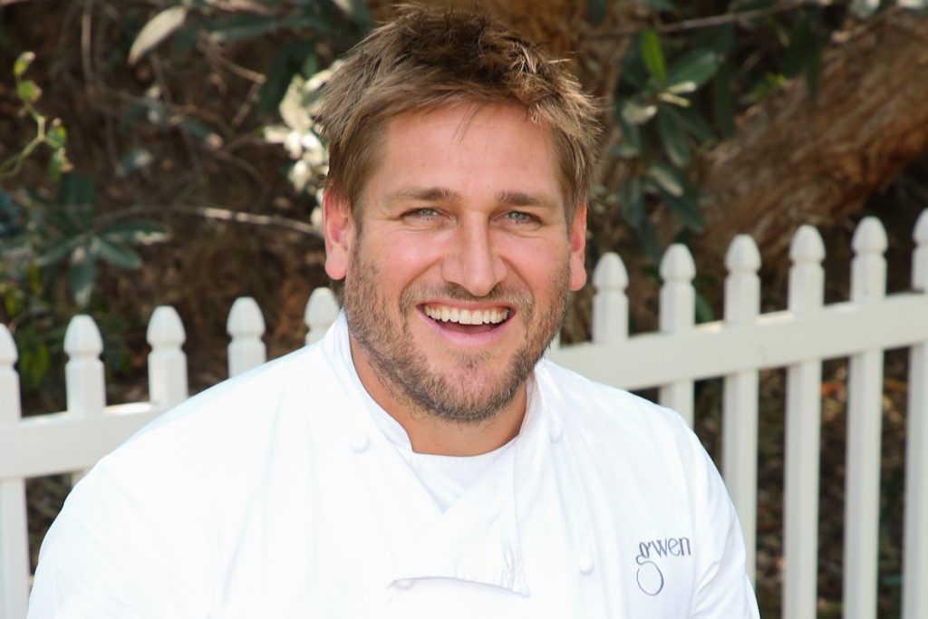 Curtis Stone wears a chef's coat and smiles at the camera.