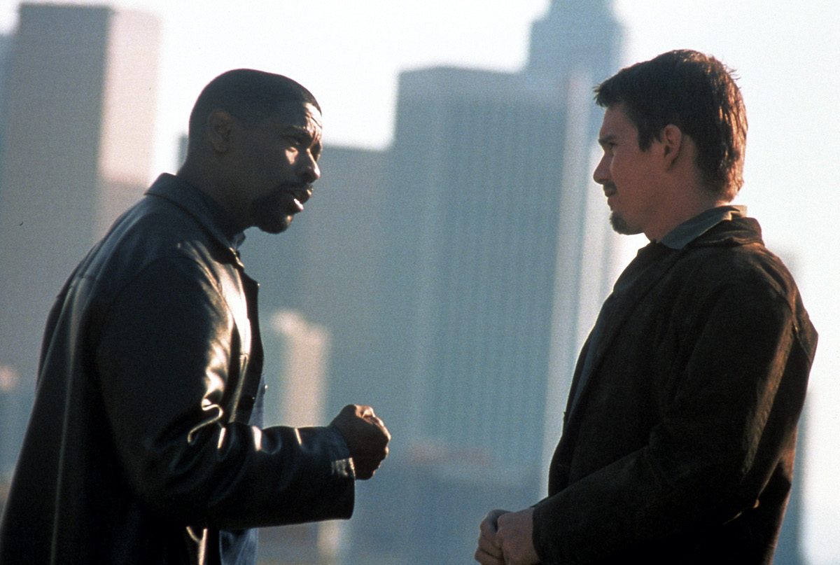 Alonzo Harris (Denzel Washington) talks to Jake Hoyt (Ethan Hawke) amid a cityscape in the movie 'Training Day'