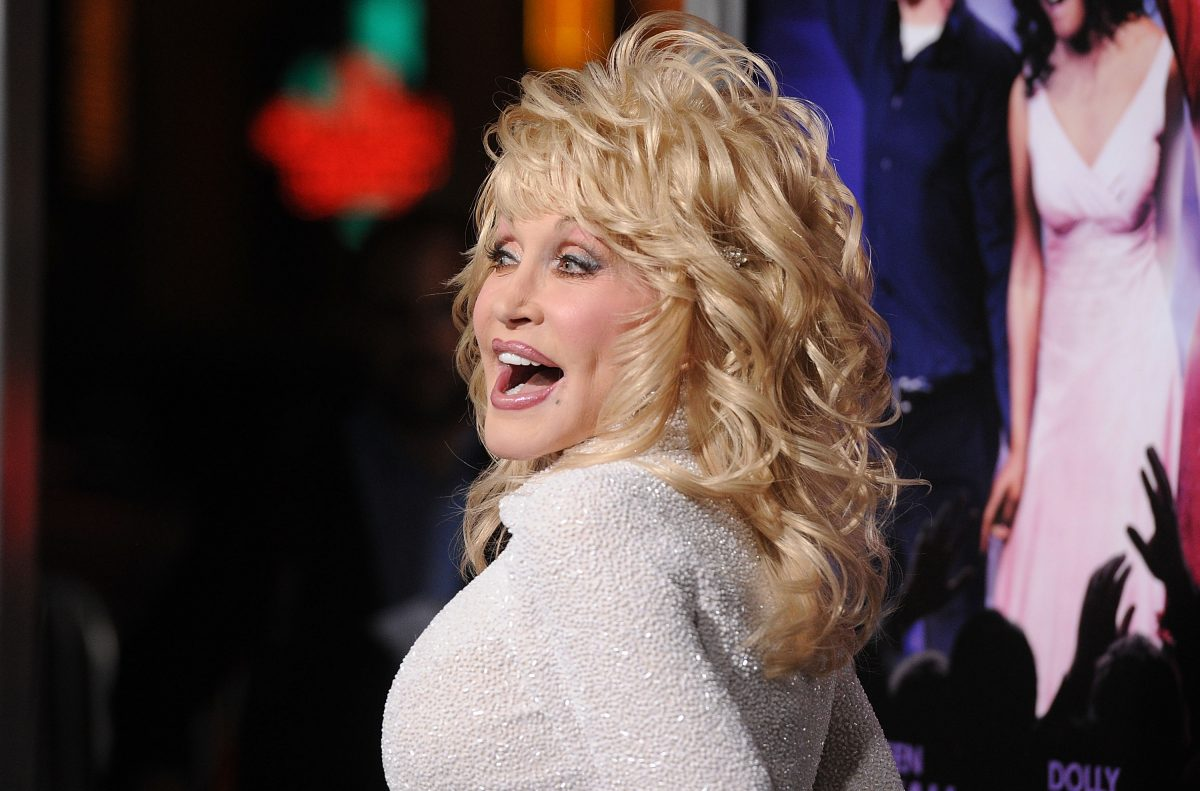 Dolly Parton photographed at the 'Joyful Noise' premiere. She's in an all-white outfit and a big, blonde wig.