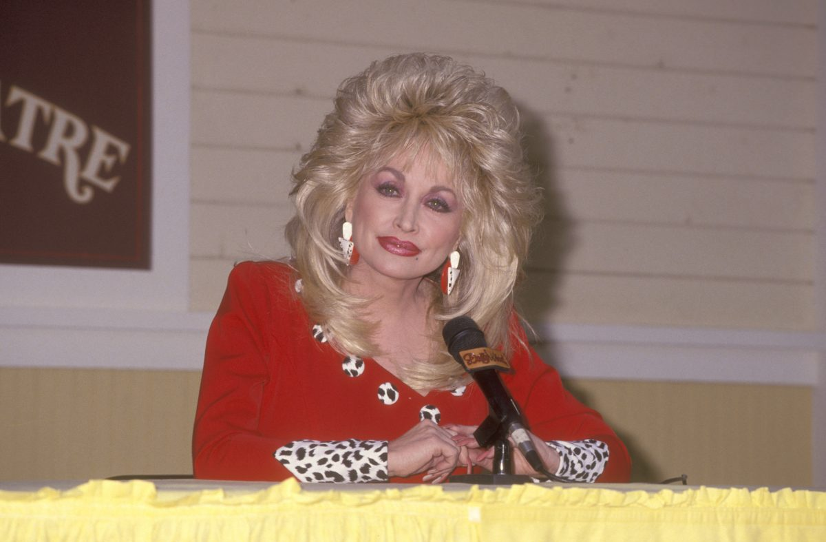 Dolly Parton sits in front of a microphone in a red dress at the Opening Weekend Celebration of Dollywood on April 24, 1993 at Dollywood in Pigeon Forge, Tennessee.