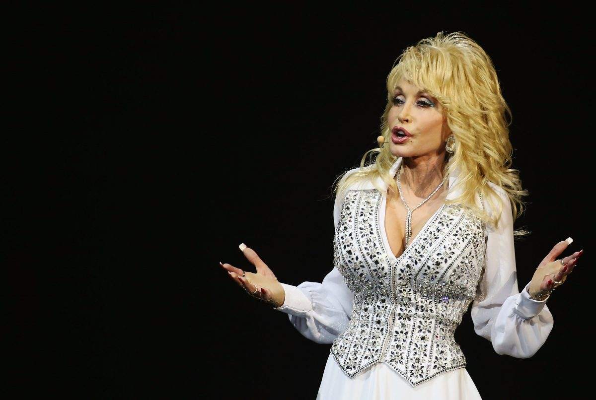 Dolly Parton on tour in Sydney, Australia. She's on stage in an all-white outfit.