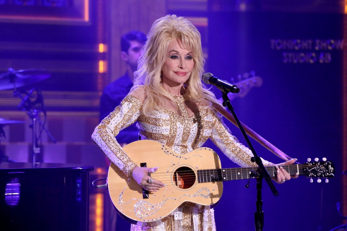 Dolly Parton on stage at 'The Tonight Show.' She's holding a guitar.
