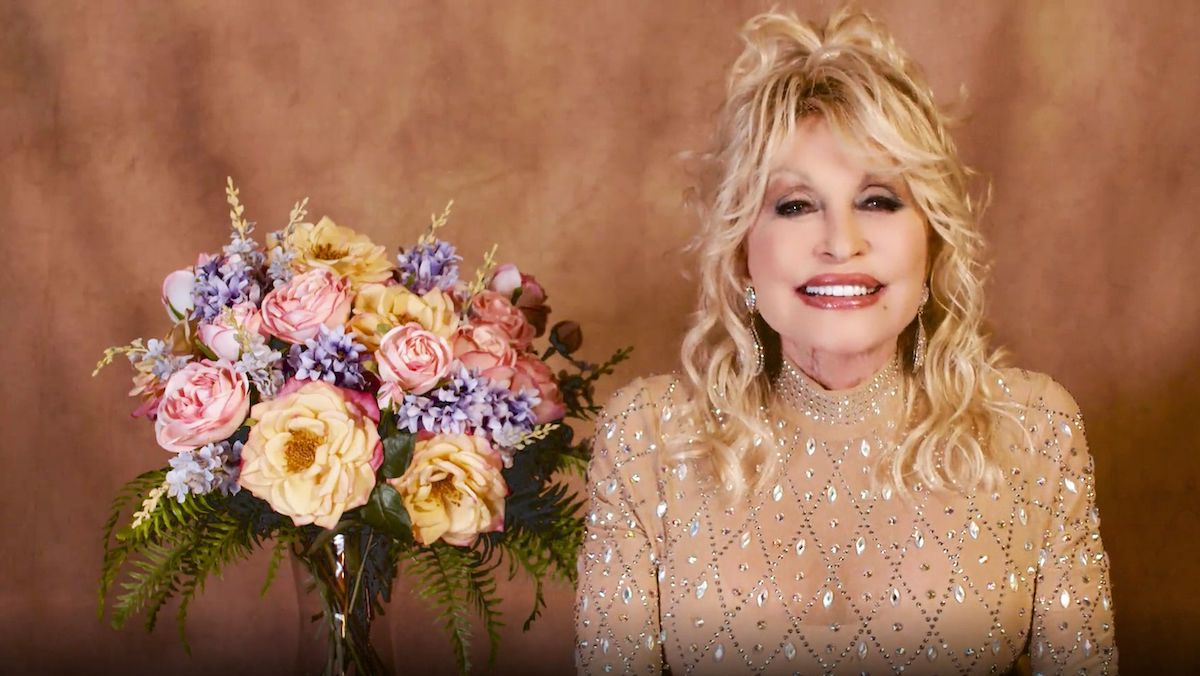 Dolly Parton beams at the camera while wearing a bejeweled nude gown