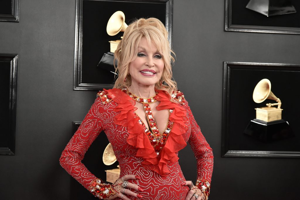 Dolly Parton smiling in a red dress on the carpet at the 61st Annual Grammy Awards