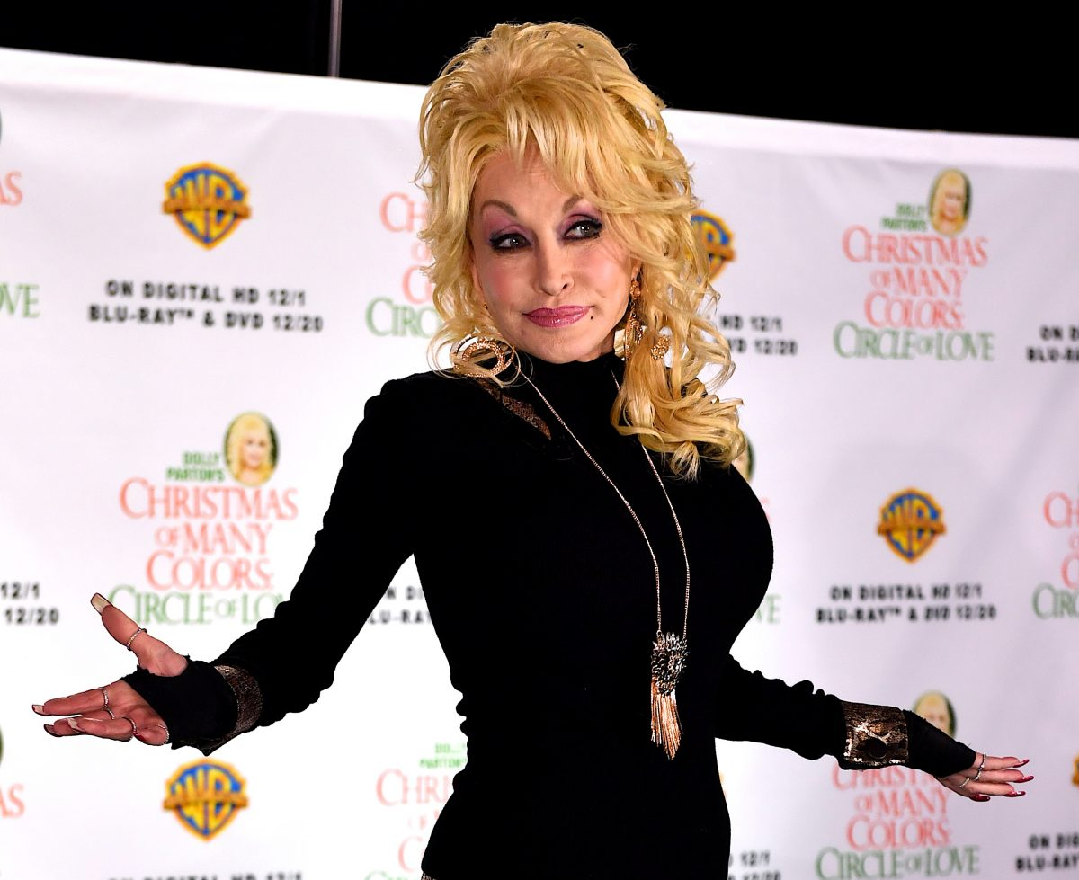 Dolly Parton poses for a photo at a press conference in 2016. She's in an all-black outfit with big, blonde hair.