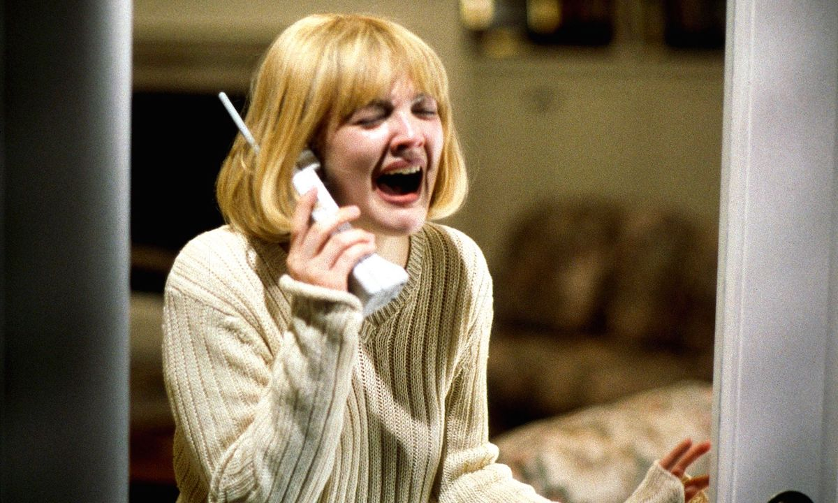 Casey Becker (Drew Barrymore) wears a white sweater and screams while holding a phone in 'Scream'