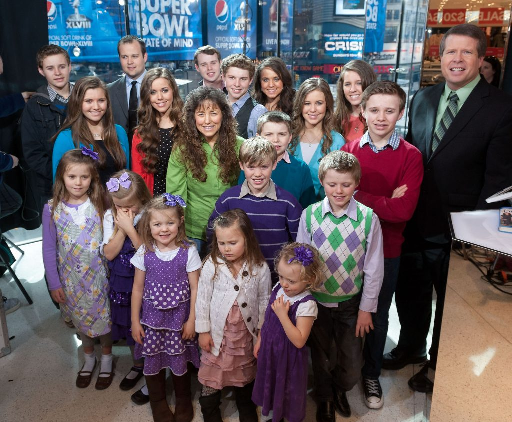 The Duggar family from TLC's 'Counting On' standing together while looking up at the camera and smiling on the set of 'Extra'