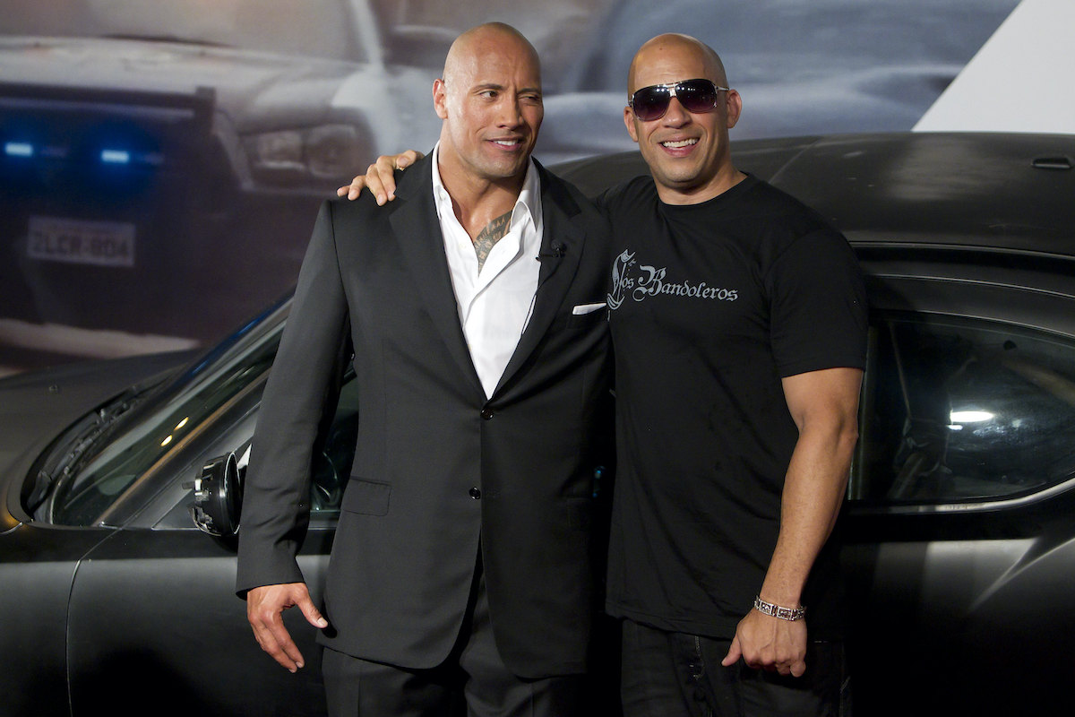 'Fast Five' co-stars Dwayne Johnson and Vin Diesel pose in front of a black car