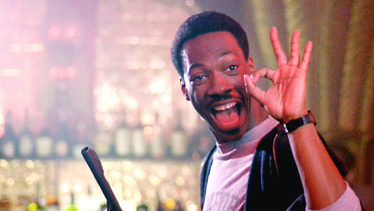 Eddie Murphy as Axel Foley in 'Beverly Hills Cop' makes the okay sign with his hand while holding a gun