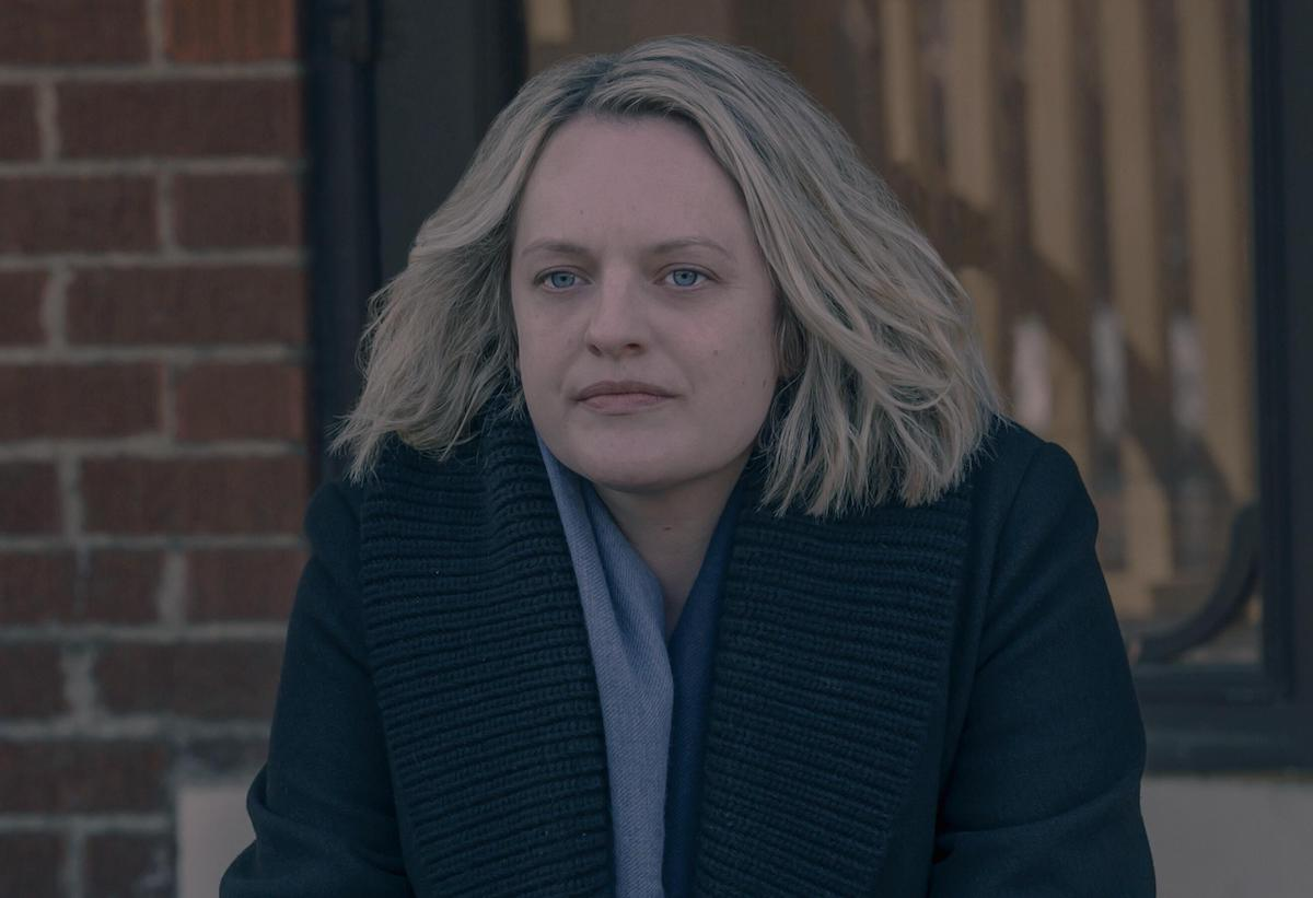 Elisabeth Moss sits on a stoop wearing a light blue scarf and black coat as June in 'The Handmaid's Tale' Season 4. In this scene, June contemplates her future and how it could change based on what she decides to do about Fred Waterford.