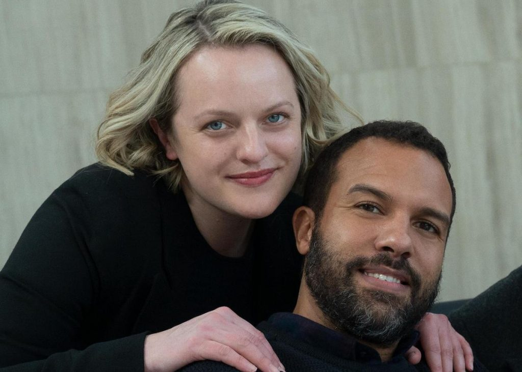 Elisabeth Moss and O-T Fagbenle pose and smile for a photo on set of 'The Handmaid's Tale' Season 4 Episode 8, 'Testimony'. Both are wearing black. Moss rests her hands on Fagbenle's shoulders.