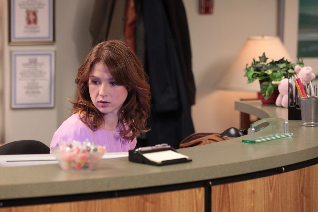 Ellie Kemper as Erin Hannon at the reception desk in a scene from 'The Office'
