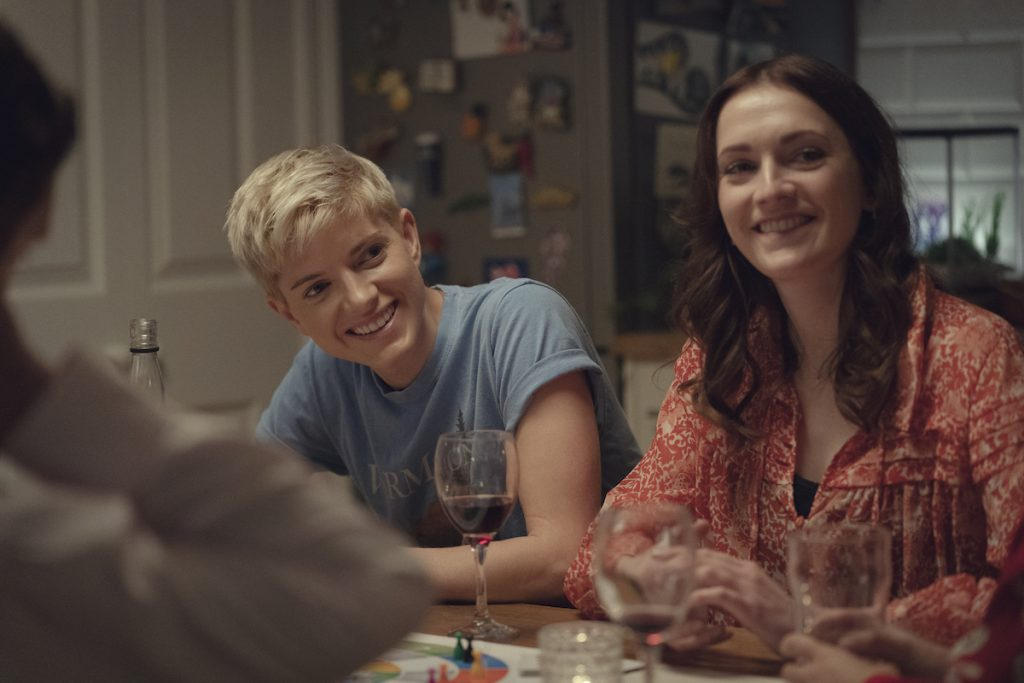 Mae Martin and Charlotte Ritchie sit at a dinner table smiling on 'Feel Good'