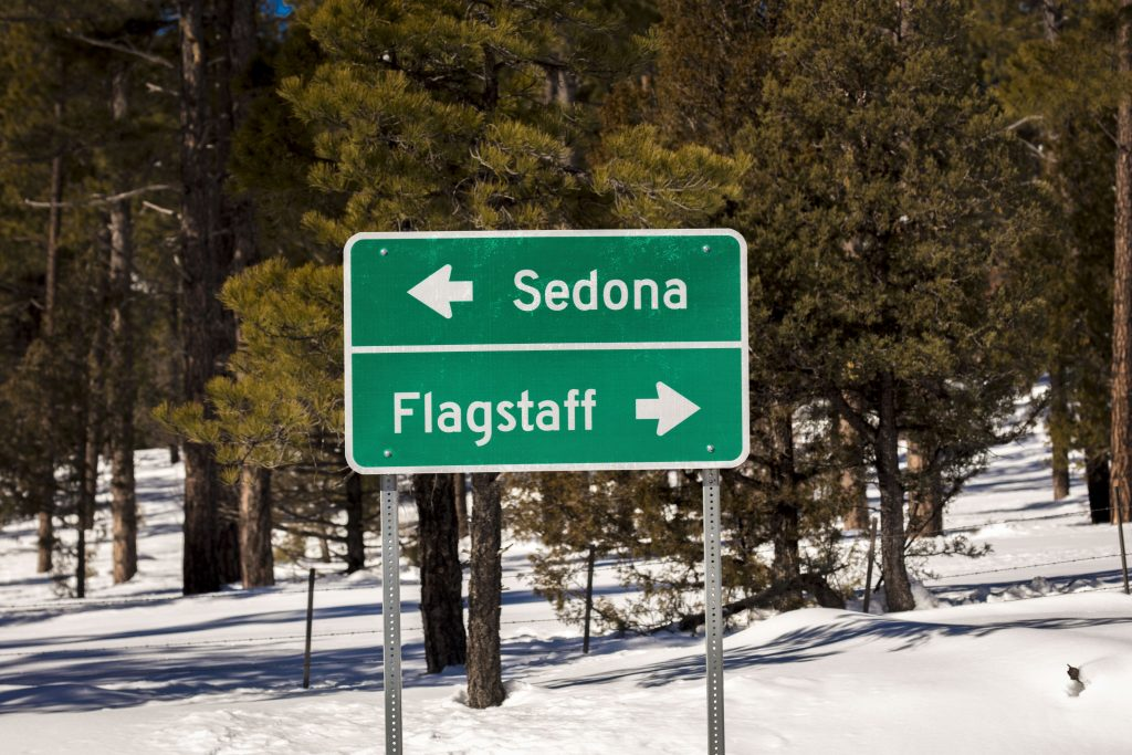 A standard road sign shows the way to Flagstaff Arizona and Sedona