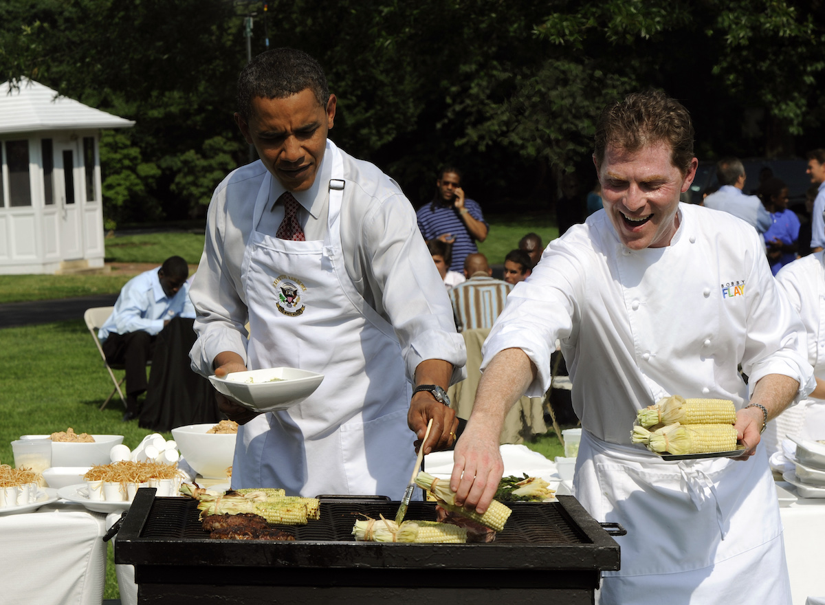 Former president Barack Obama and Bobby Flay grilling corn on the cob