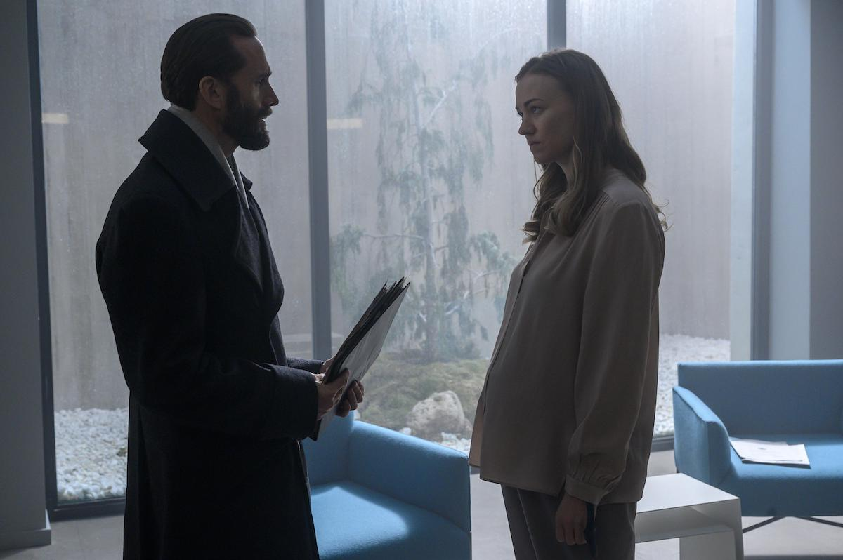 Joseph Fiennes as Fred Waterford in a long, black, wool coat holding a folder of paperwork. He stands across from Yvonne Strahovski as Serena Joy Waterford, who is pregnant and wears a light pink blouse and light grey pants in 'The Handmaid's Tale' Season 4. They stand in an elite prison cell with floor-to-ceiling windows and blue chairs. Natural light is coming through the windows and a small tree is seen through it.