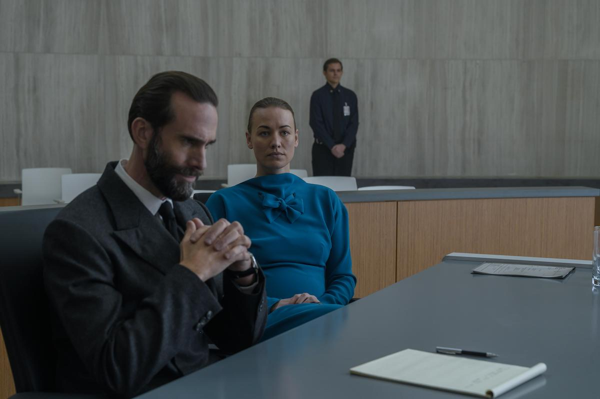 Joseph Fiennes as Fred Waterford and Yvonne Strahovski as Serena Joy Waterford in 'The Handmaid's Tale' Season 4. He wears a dark grey suit and crosses his hands in concern while sitting at a table in a court room. She wears a teal dress and looks straight ahead while sitting next to him.
