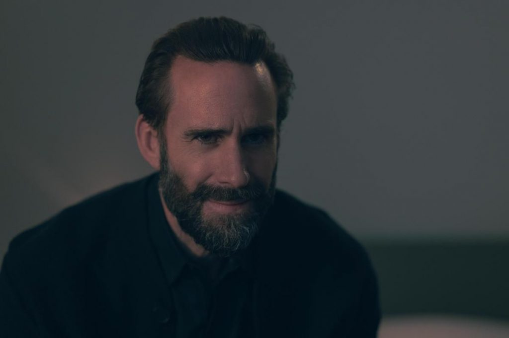 Joseph Fiennes as Fred Waterford wearing a black shirt, black sweater, and black tie in front of a beige wall in 'The Handmaid's Tale' Season 4