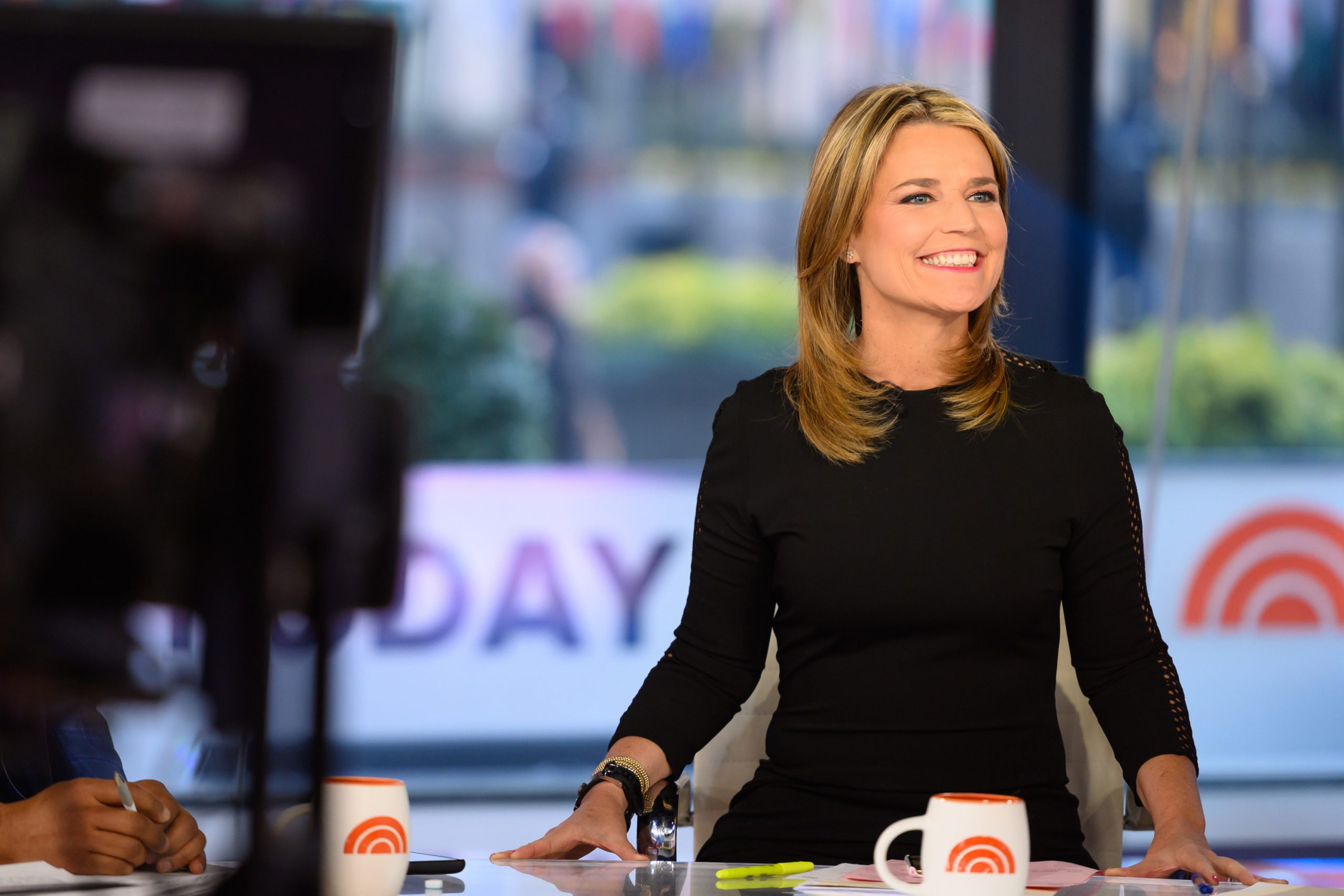 Morning show co-host Savannah Guthrie smiles as she sits at her anchor chair on the set of 'Today' in a long-sleeved black dress.