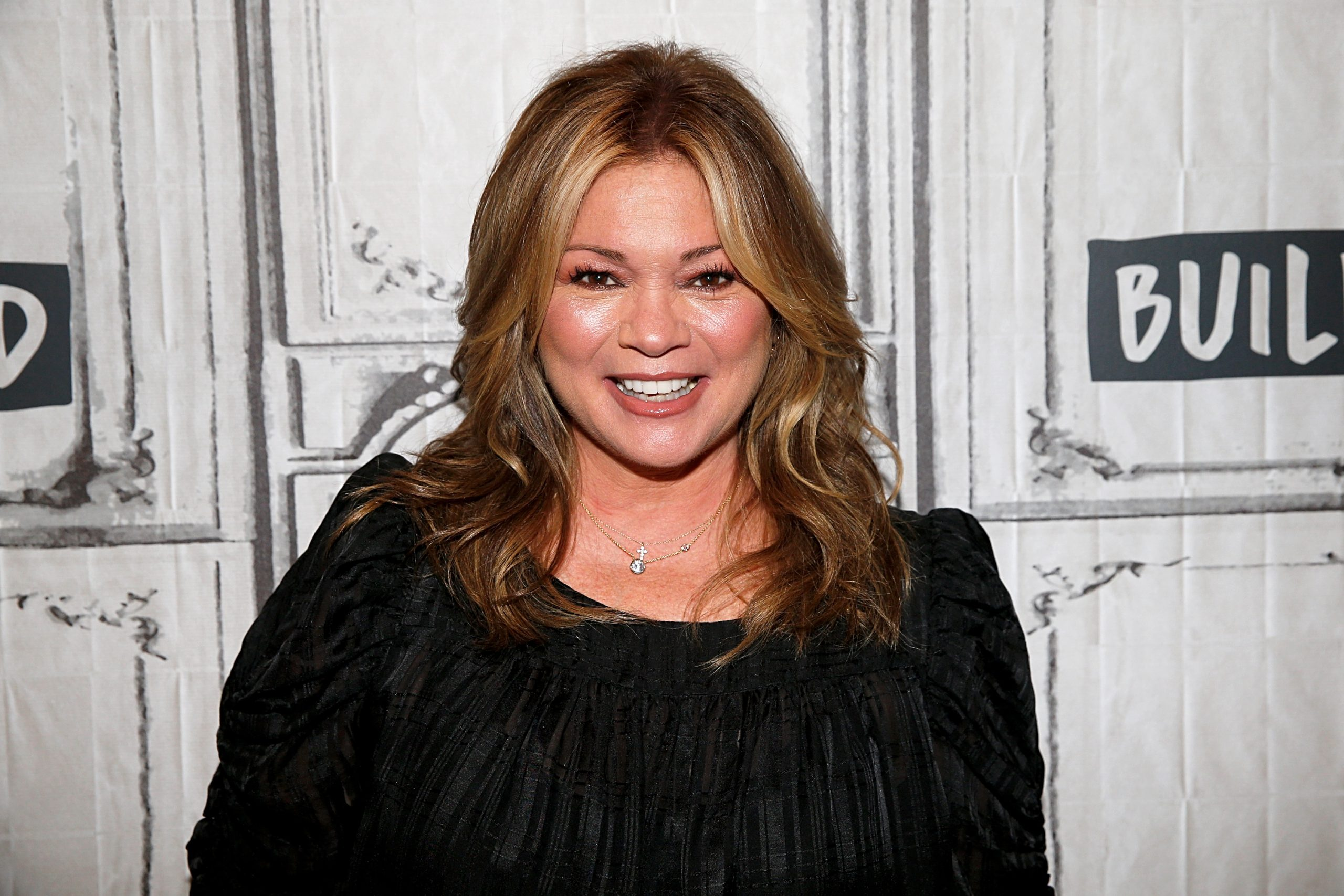 Food Network star Valerie Bertinelli is wearing a dark long-sleeved top and smiling for the camera.