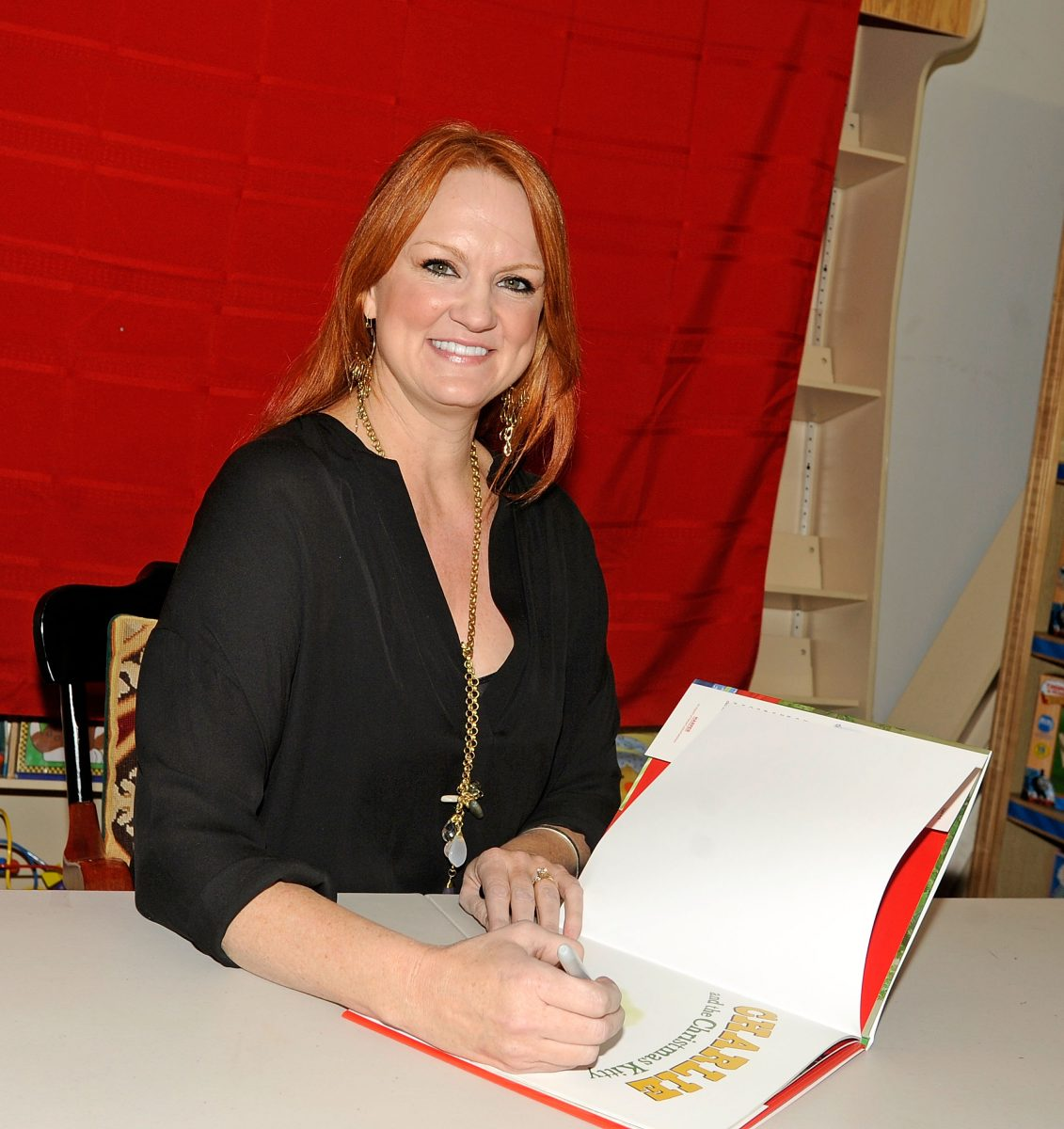The Pioneer Woman Ree Drummond smiles as she signs a cookbook at a 2012 book signing
