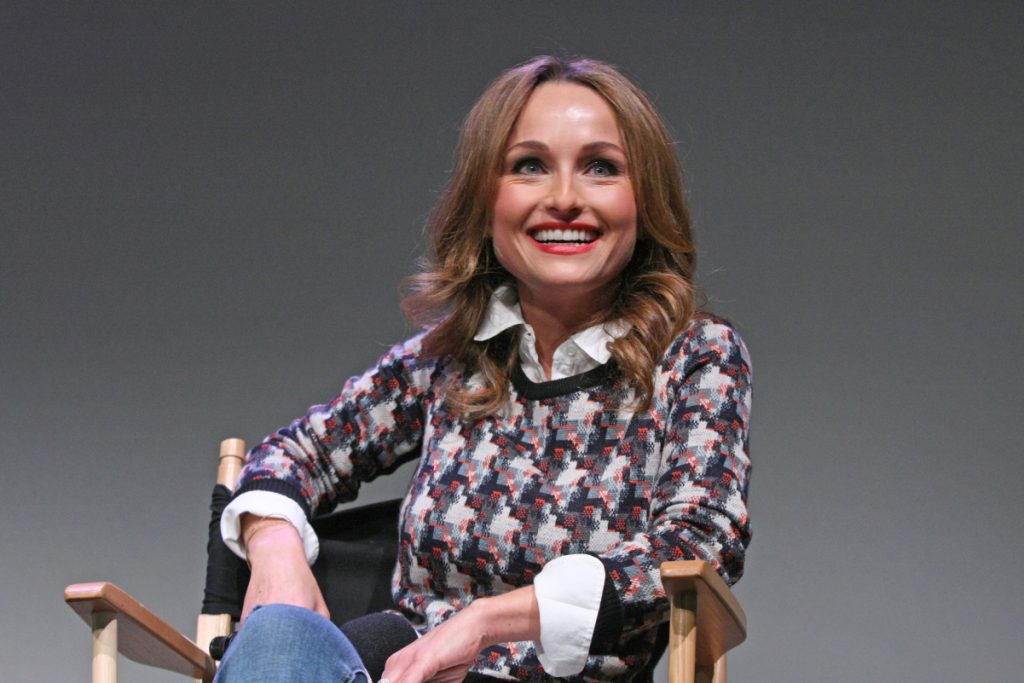Food Network star Giada De Laurentiis smiles at a public appearance in a multi-colored sweater and jeans.