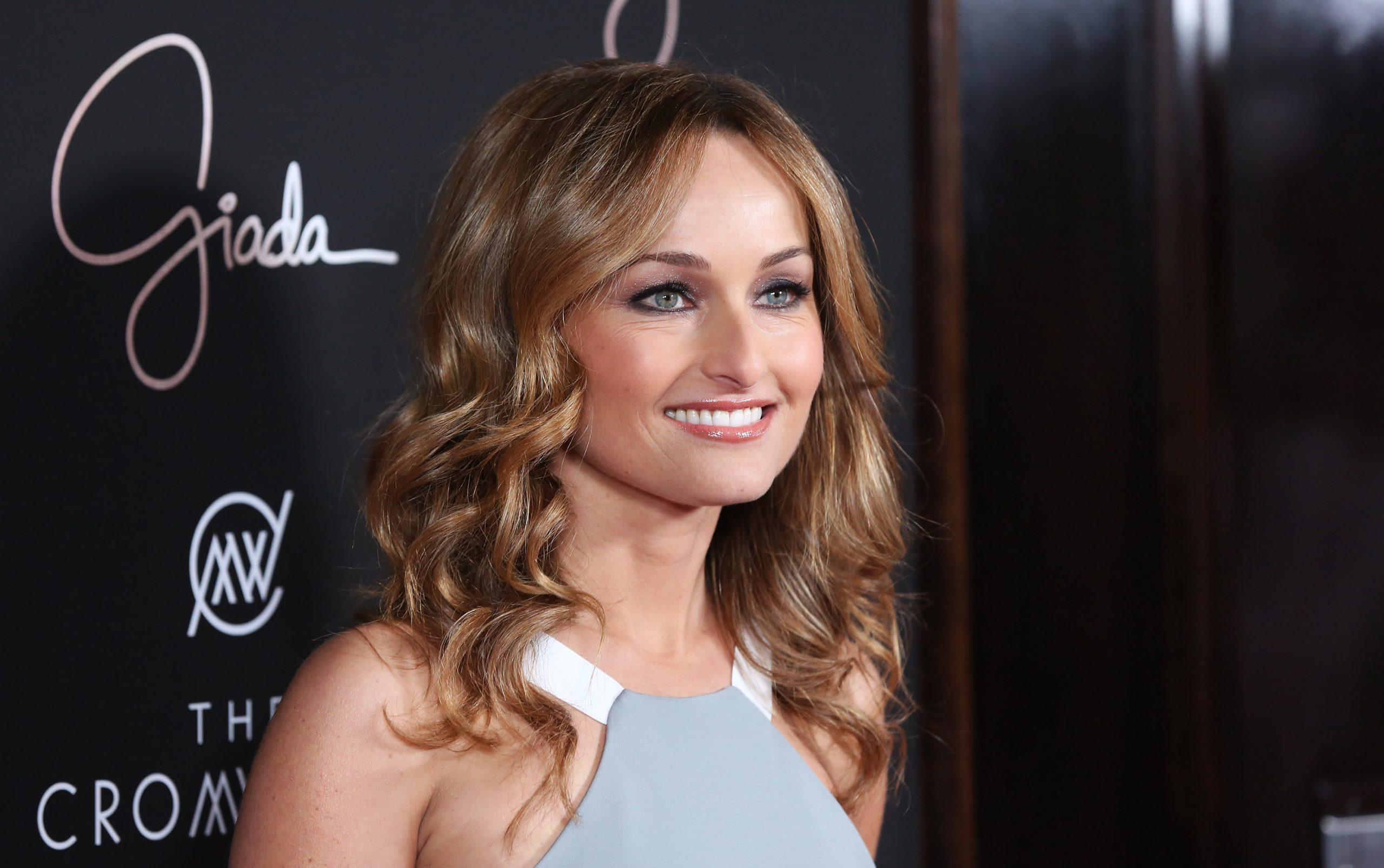 Food Network star Giada De Laurentiis smiles as she wears a sleeveless gray dress at a 2014 restaurant opening.