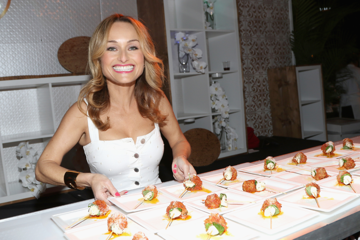 Celebrity chef Giada De Laurentiis smiles at the camera while she prepares a dish wearing a white sleeveless dress