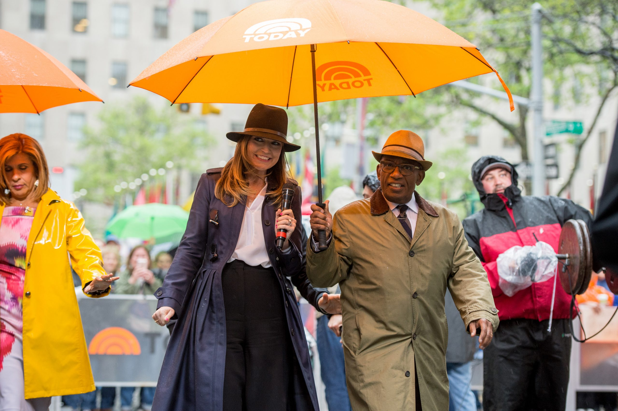 Savannah Guthrie wears a hat and shares a yellow umbrella with her 'Today' co-host Al Roker, also donning a hat.