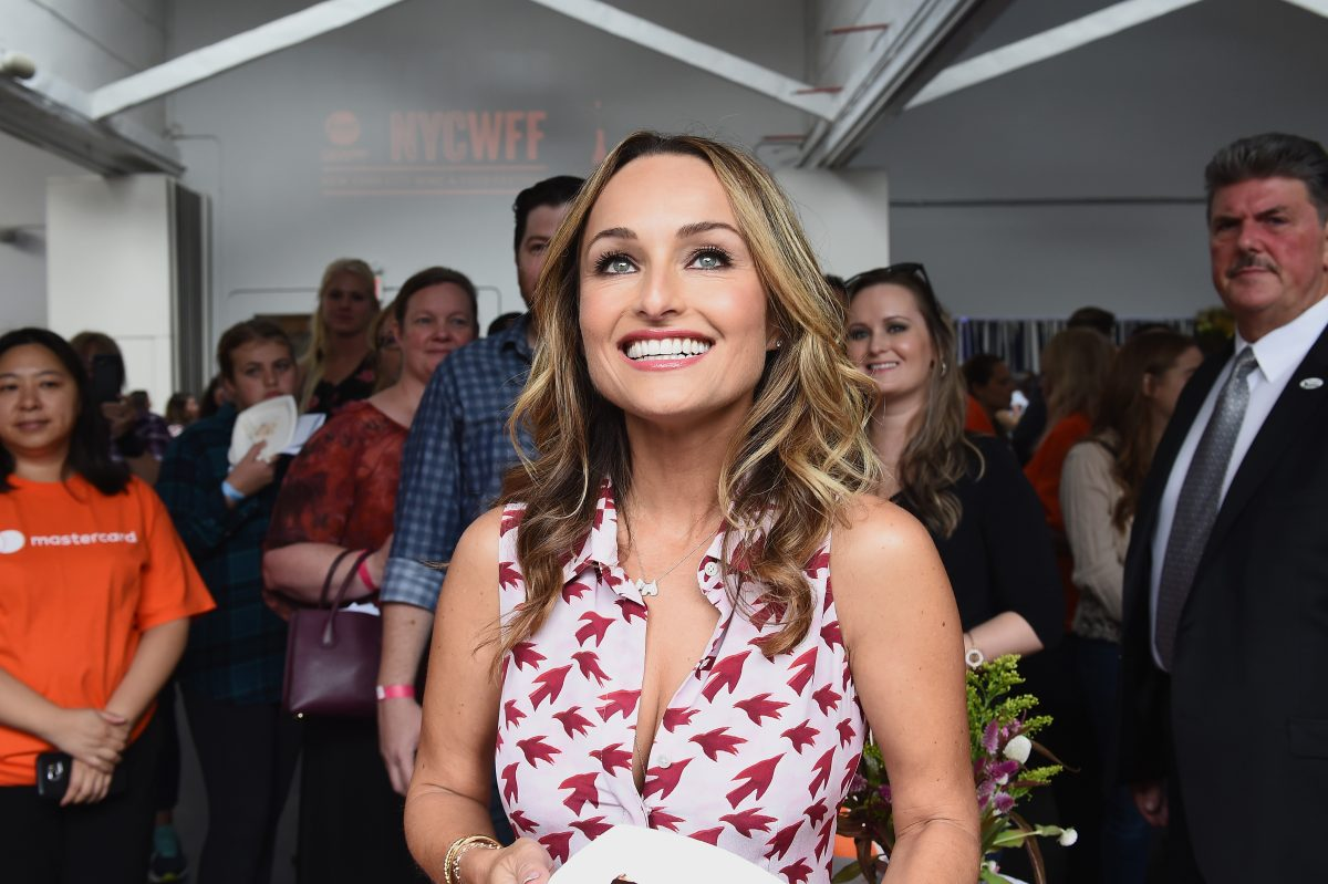 Giada De Laurentiis smiles while holding a dish of food at the Food Network & Cooking Channel New York City Wine & Food Festival