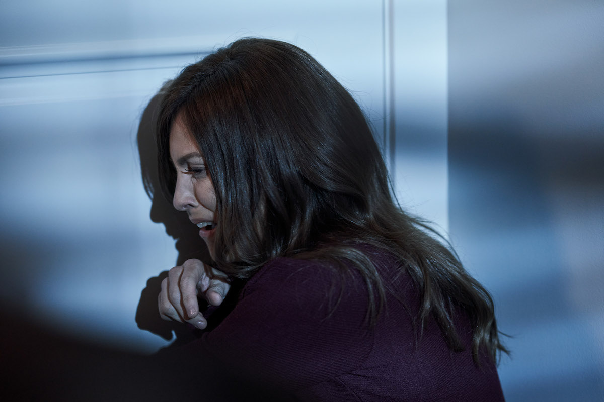 Crying Jennifer Dulos leaning against door in Lifetime movie Gone Mom