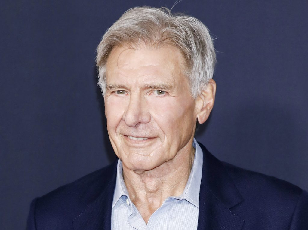 Harrison Ford smiles in a navy blue suit and light blue button-down shirt in front of a blue-grey background.