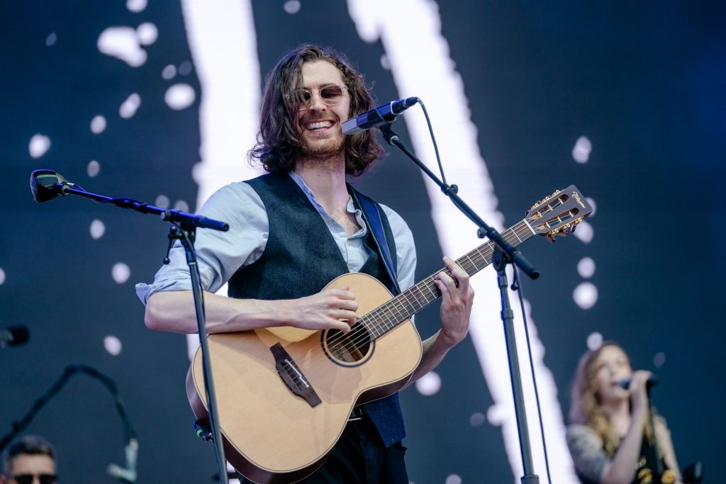 Hozier smiling, holding a guitar, on stage