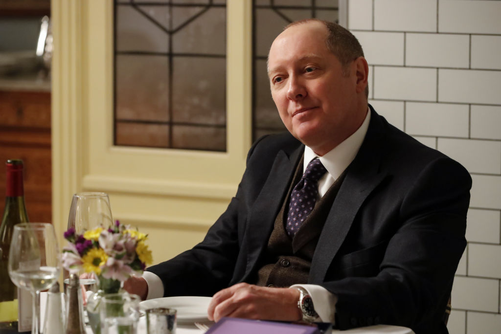 James Spader as Raymond 'Red' Reddington looks across the table he's sitting at with a smirk.
