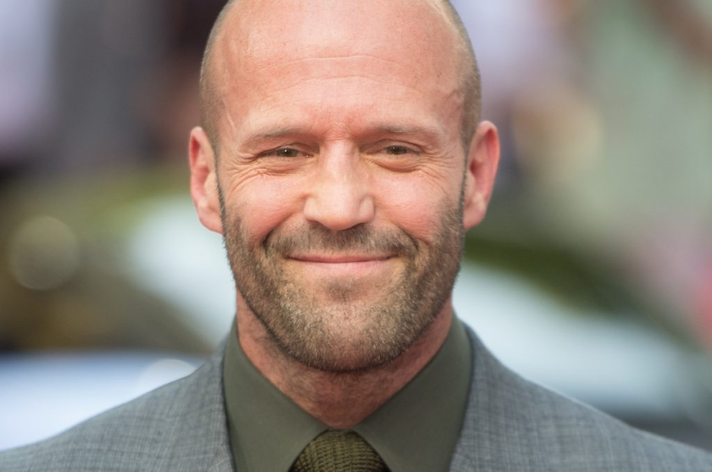 Jason Statham wears a suit and smiles at a 'Fast & Furious Presents: Hobbs & Shaw' screening