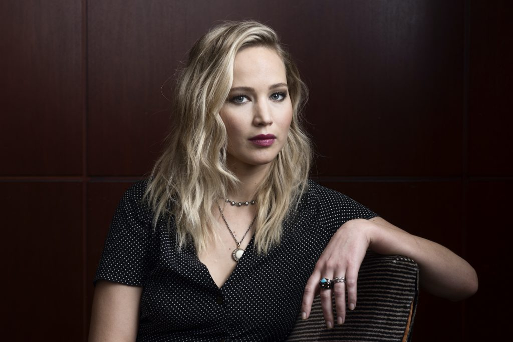 Jennifer Lawrence smiling in front of a wood paneled wall