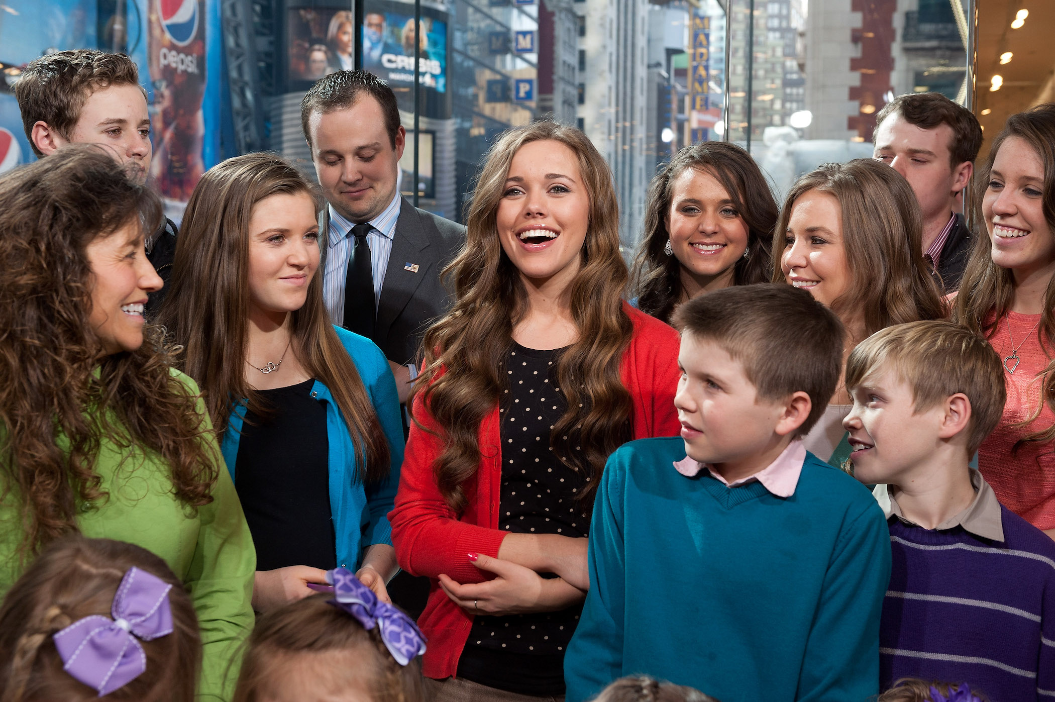 Jessa Duggar, in a red cardigan, surrounded by members of the Duggar family during a 2014 appearance on 'Extra.'