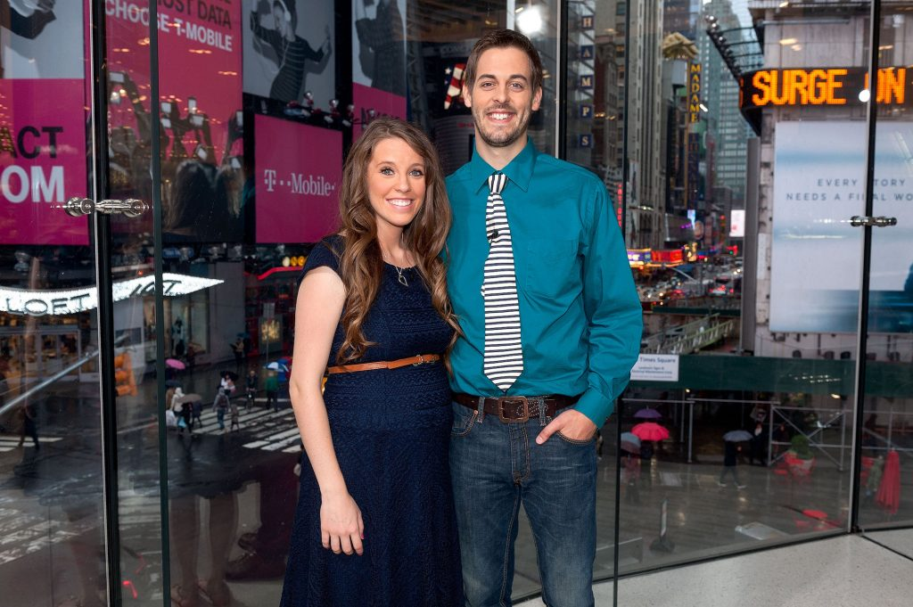 Jill Duggar Dillard (L) and husband Derick Dillard of the Duggar family standing together and smiling on the set of 'Extra'