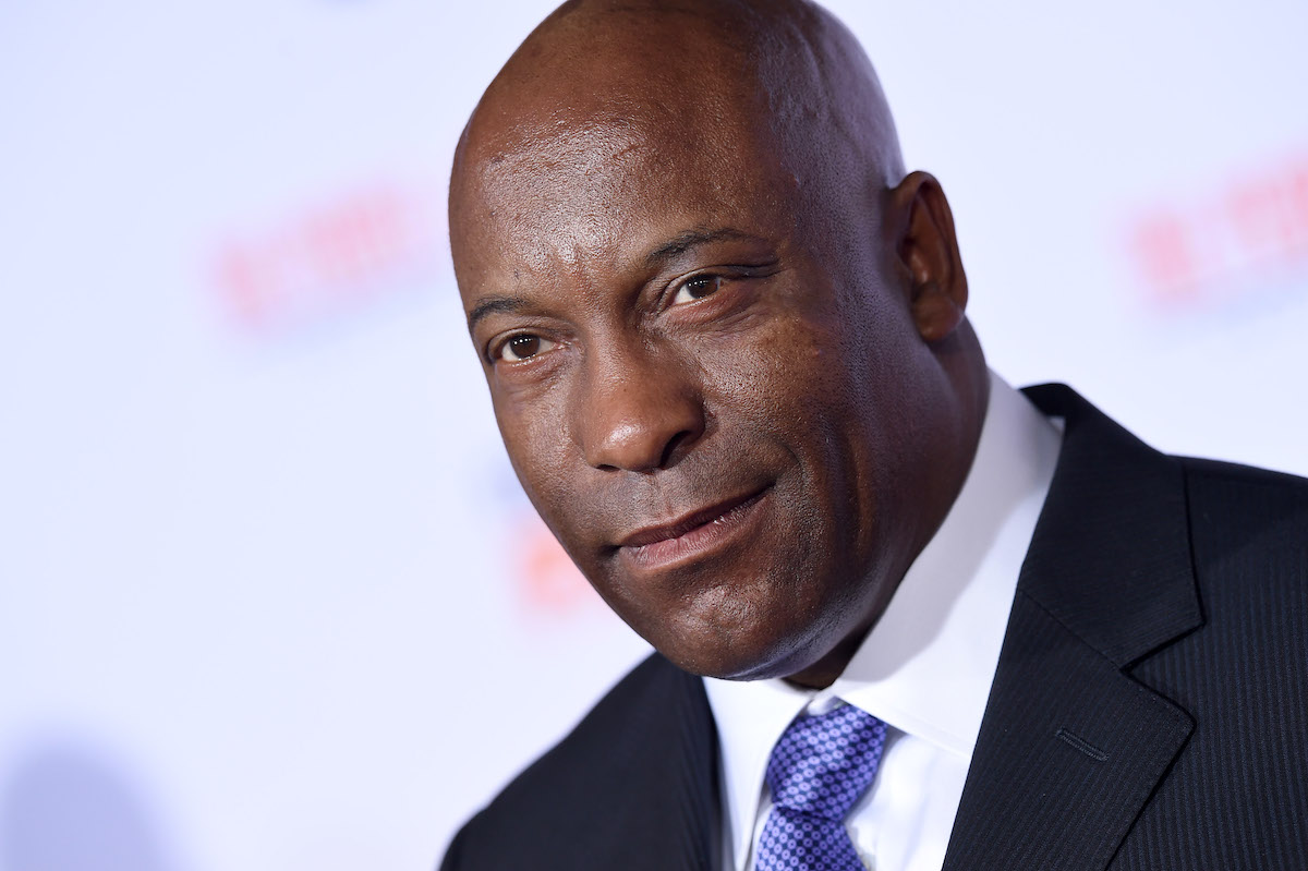John Singleton wears a suit and tie on the red carpet