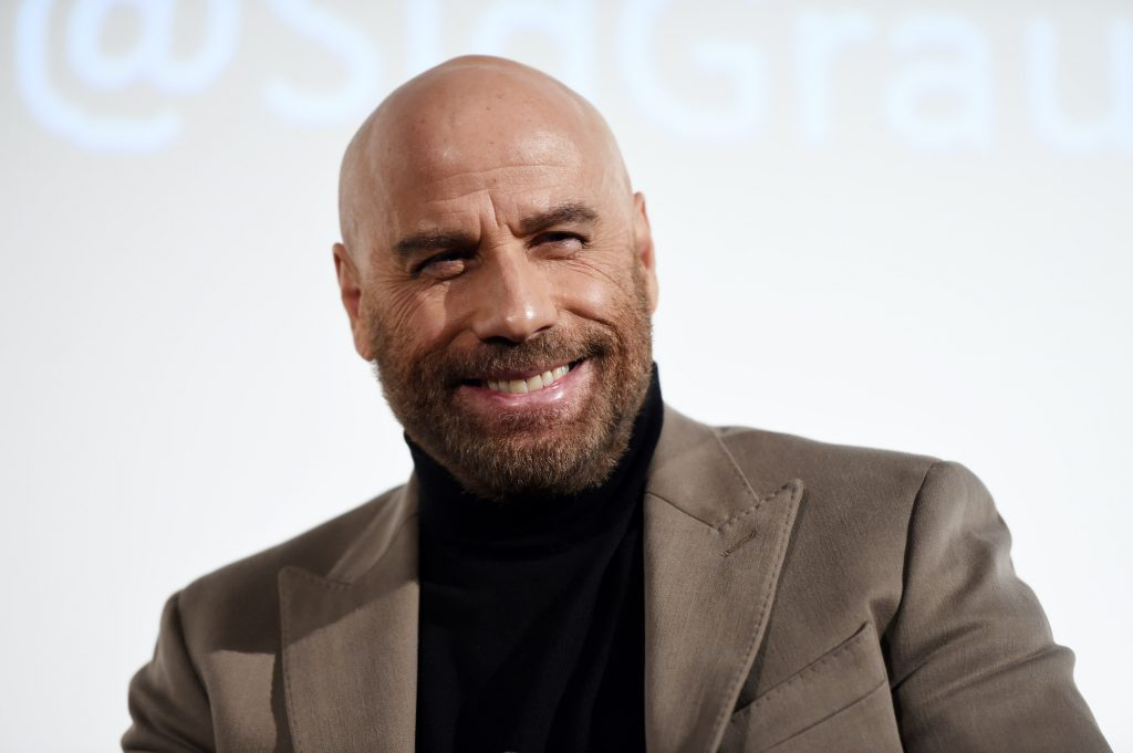 John Travolta smiling in front of a white background