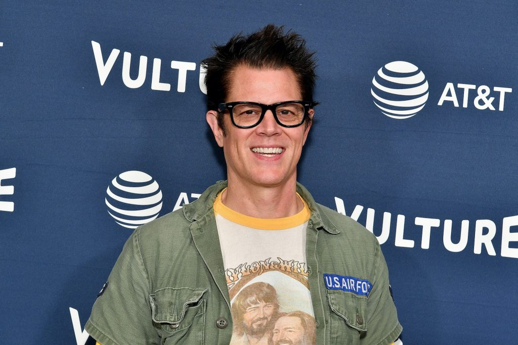 Johnny Knoxville smiling in front of a blue background