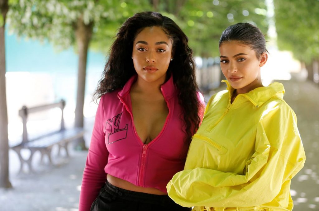 Jordyn Woods in a pink jacket and Kylie Jenner in a yellow jacket