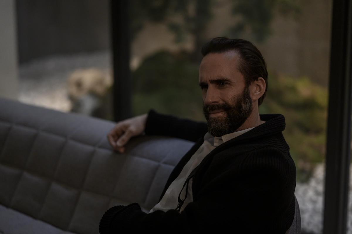 Joseph Fiennes as Fred Waterford in 'The Handmaid's Tale' Season 4. He sits on a grey couch in a high-end prison cell with floor-to-ceiling windows. He wears a white button-down shirt and black sweater, his arm is on the back of the couch.