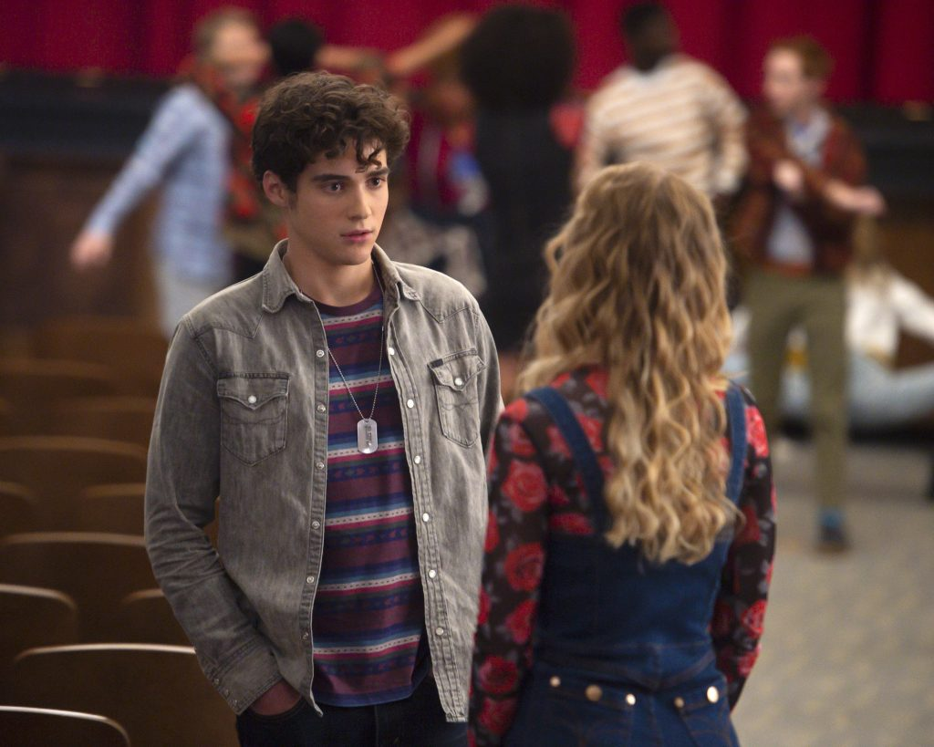Joshua Bassett in the Disney+ original series 'High School Musical: The Musical: The Series' as Ricky Bowen, dressed in a gray jacket talking to another character