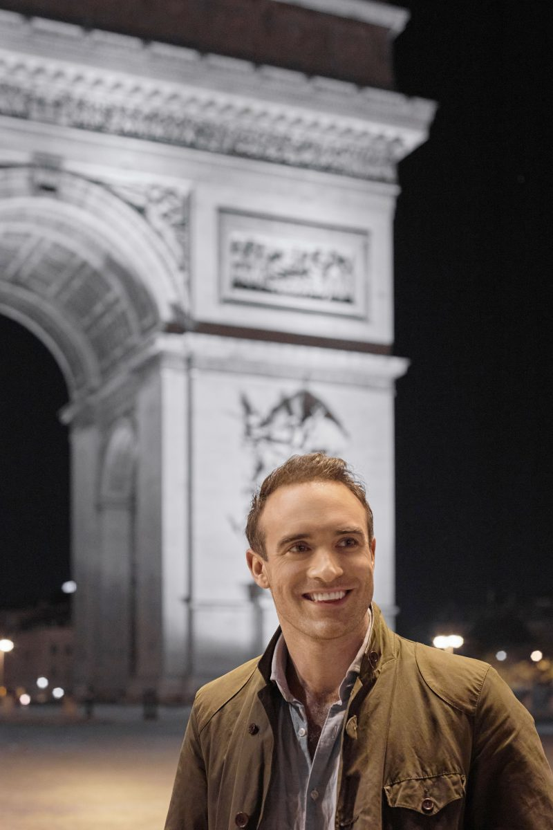 Joshua Sasse in front of the Arc de Triomphe in 'Her Pen Pal'