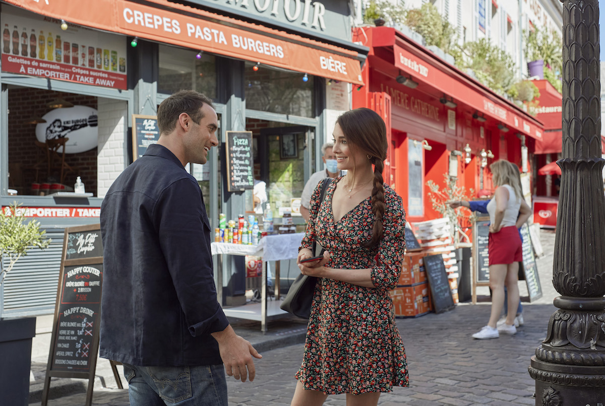 Joshua Sasse and Mallory Jansen standing in front of food stalls in Paris in 'Her Pen Pal'