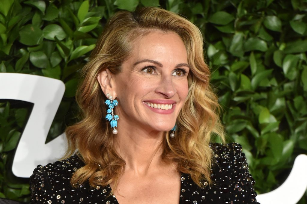Julia Roberts smiling in front of a green background