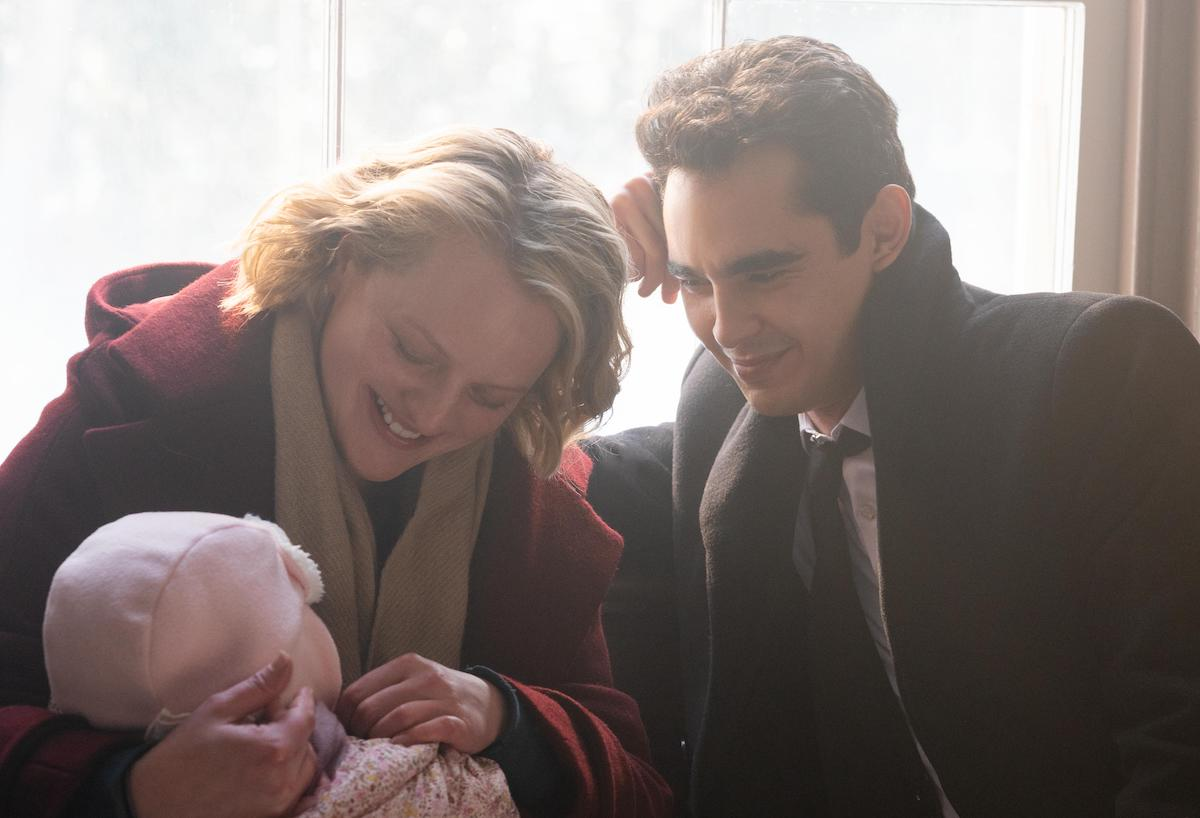 Elisabeth Moss wears a red wool coat and beige scarf as June and Max Minghella wears a black wool coat, black suit, white shirt, and black tie as Nick in 'The Handmaid's Tale' Season 4. They smile down at baby Nichole, wearing all pink. And they're sitting in front of a sun-filled window.