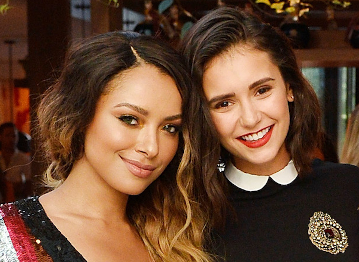 'The Vampire Diaries' stars Kat Graham and Nina Dobrev pose for a photo. Graham wears a multicolored sequin dress and Dobrev wears a black dress with a white collar and gold brooch.